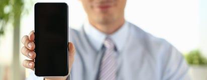Um homem de neg?cios guarda um smartphone novo imagem de stock