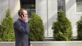 Um homem de neg?cios novo que anda abaixo da rua e comunica-se felizmente no telefonema filme
