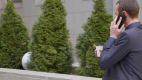 Um homem de neg?cios novo que anda abaixo da rua e comunica-se felizmente no telefonema video estoque