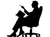 Um homem de negócio com a agenda pessoal que toma as notas que sentam-se na AR Foto de Stock