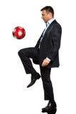 Um homem de negócio que joga a bola de futebol de mnanipulação Imagens de Stock