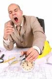 Um homem de negócios sonolento com plantas arquitectónicas Imagem de Stock