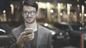 Um homem de sorriso é guardando e de vista seu telefone celular na rua Fotografia de Stock