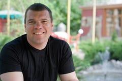 Um homem de sorriso em um café no verão fora fotos de stock