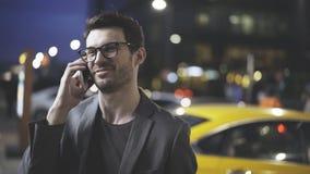 Um homem de sorriso está tendo uma noite chama a rua Fotos de Stock