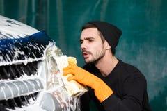 Um homem de sorriso lava um carro cinzento imagem de stock