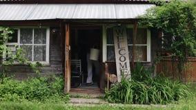 Um homem de sorriso novo com as duas cubetas vazias que anda fora da casa de madeira pequena Na vila Sinal bem-vindo vazio filme
