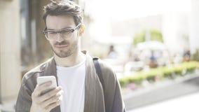 Um homem de sorriso novo enrola o telefone na rua Imagem de Stock