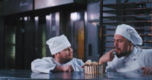 Um homem de vista robusto do padeiro picaretas vestindo de um vestuário dos cozinheiros chefe neste bolo irresistível e um homem  video estoque