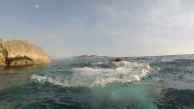 Um homem decola em um goprote que está nas rochas e que olha o mar os povos no fundo estão descansando clear vídeos de arquivo