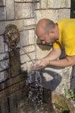 Um homem derrama em suas mãos molha de uma fonte da montanha para beber foto de stock royalty free