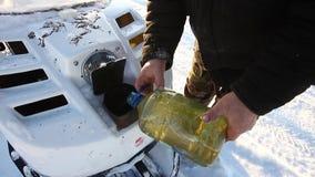 Um homem derrama o óleo em um carro de neve filme