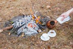 Um homem derrama o café de um potenciômetro turco de terra em copos brancos pequenos em uma floresta da fogueira na primavera foto de stock