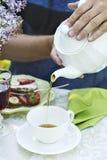 Um homem derrama o chá em um copo fotos de stock
