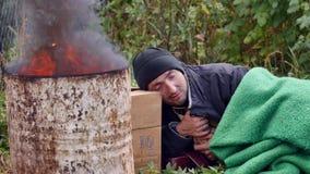 Um homem desabrigado que dorme perto do fogo filme
