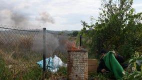 Um homem desabrigado que dorme perto do fogo video estoque