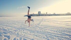 Um homem desencapado-chested faz um movimento da carro-roda na neve vídeos de arquivo