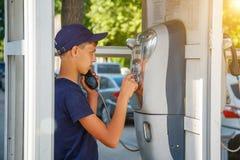 Um homem disca um número de telefone em uma cabine de telefone fotografia de stock royalty free