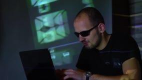 Um homem do hacker do homem nos óculos de sol em uma sala escura trabalha com o código do programa video estoque