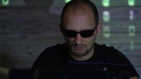 Um homem do hacker do homem nos óculos de sol em uma sala escura trabalha com o código do programa filme