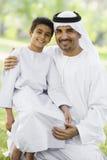 Um homem do Oriente Médio e seu filho que sentam-se em um parque imagens de stock royalty free