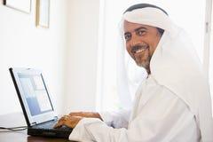 Um homem do Oriente Médio na frente de um computador fotos de stock royalty free