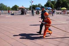 Um homem do ` s do bombeiro está ensinando uma menina em um terno à prova de fogo ornery correr ao redor com Bielorrússia, Minsk, fotografia de stock royalty free