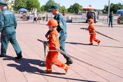 Um homem do ` s do bombeiro está ensinando uma menina em um terno à prova de fogo ornery correr ao redor com Bielorrússia, Minsk, foto de stock