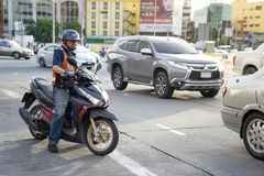 Um homem do táxi do velomotor da entrega está livrando um ciclo de motor em s ocupado imagens de stock royalty free