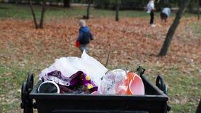 Um homem e seu filho limpam o lixo em um parque público O conceito do inquietação com o ambiente e do inquietação com o ambiente  vídeos de arquivo