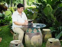 Um homem e sua tabuleta sentam-se no jardim Imagens de Stock Royalty Free