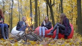 Um homem e três mulheres estão sentando-se em tamboretes acolchoados em uma floresta do outono em torno de um fogo e estão guarda filme