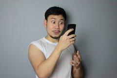 Um homem e um telefone celular Fotografia de Stock