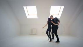 Um homem e uma dança da mulher uma dança sensual da salsa ou do bachata em um estúdio branco video estoque