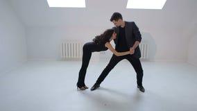 Um homem e uma dança da mulher uma dança sensual da salsa ou do bachata em um estúdio branco vídeos de arquivo