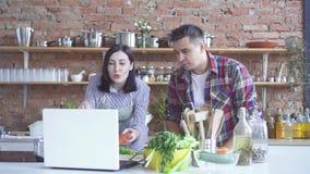 Um homem e uma família da mulher estão preparando uma lição video na cozinha ao olhá-la em um portátil branco filme