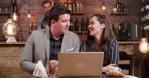 Um homem e uma jovem mulher em uma pausa para o almoço que olha o portátil e o riso filme