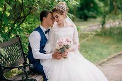 Um homem e uma mulher apenas casaram-nos estão sentando-se em um banco em um parque quieto verde A noiva no ` s do noivo dobra de imagem de stock