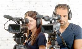 Um homem e uma mulher com câmaras de vídeo profissionais Imagem de Stock Royalty Free