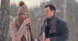 Um homem e uma mulher de amor dos pares no chá bebendo da floresta do inverno de uma garrafa térmica Homem e mulher à moda em um  filme