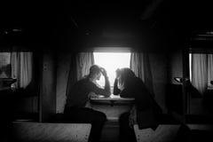 Um homem e uma mulher estão sentando-se perto de uma janela em um trem imagens de stock