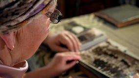 Um homem e uma mulher idosos dos pares estão olhando suas fotos velhas em casa e fala Um homem com um bigode, uma esposa com filme