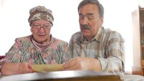 Um homem e uma mulher idosos dos pares estão olhando suas fotos velhas em casa e fala Um homem com um bigode, uma esposa com vídeos de arquivo