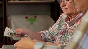 Um homem e uma mulher idosos dos pares estão olhando suas fotos velhas em casa e fala Um homem com um bigode, uma esposa com video estoque