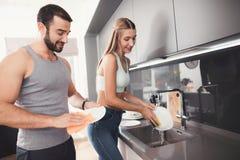 Um homem e uma mulher na cozinha na manhã Lavam os pratos após o café da manhã foto de stock