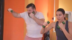 Um homem e uma mulher para dar certo um pontapé de um peso em uma sessão de formação no encaixotamento, um gym, mo lento vídeos de arquivo