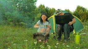 Um homem e uma mulher perto da barraca na natureza fritam o no espeto e bebem o chá Um homem está trabalhando em um portátil vídeos de arquivo