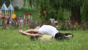 Um homem e uma mulher que esticam antes de fazer exercícios Os instrutores novos da ioga praticam em um parque da cidade na grama vídeos de arquivo