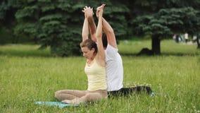 Um homem e uma mulher que esticam antes de fazer exercícios Os instrutores novos da ioga praticam em um parque da cidade na grama video estoque