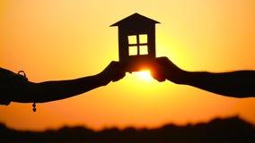 Um homem e uma mulher que mantêm uma casa de papel contra o por do sol A silhueta da casa O tema da construção, real filme